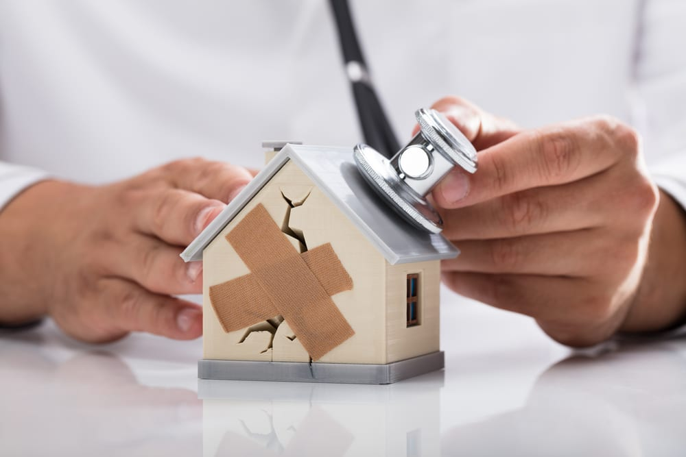 House with a stethoscope being applied to it by a doctor