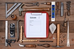 High angle shot of a contractors estimate form surrounded by his well used tools.