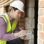 Man checking a home holding a clip board