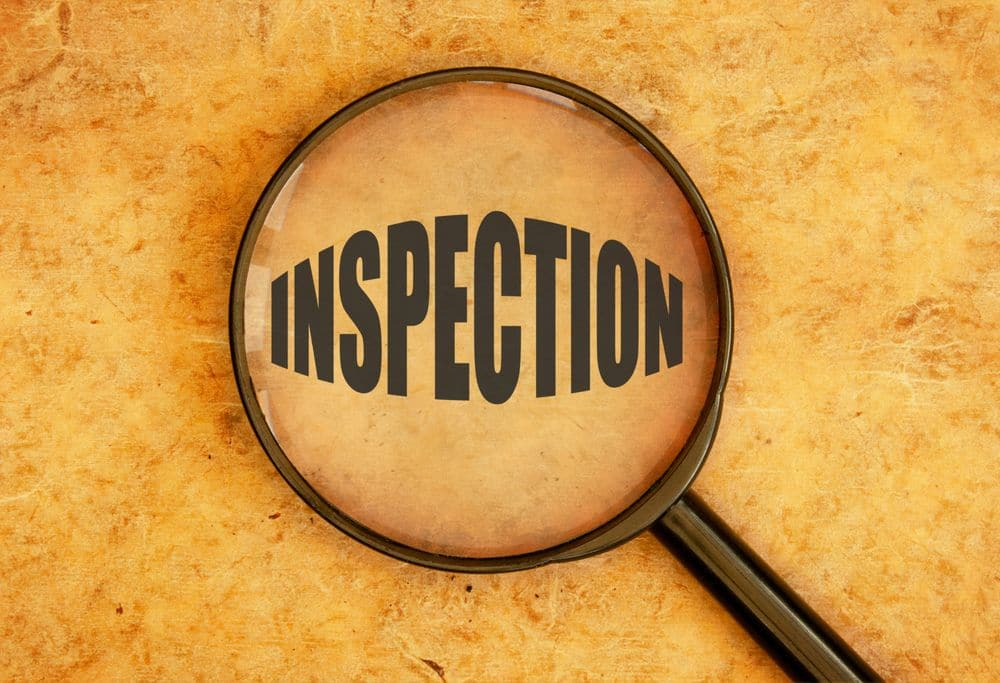 """Magnifying Glass with """"Inspection"""" inside of it."""